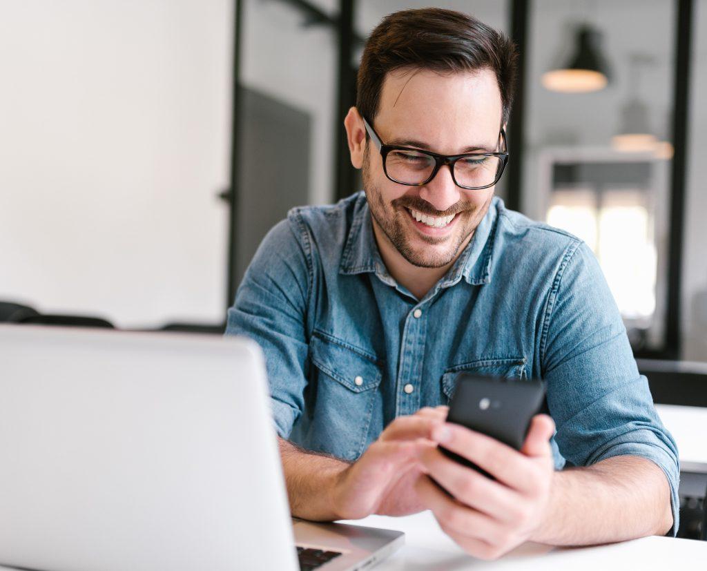 Man Using Phone and Computer